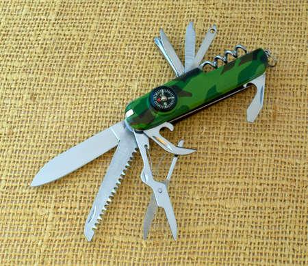 temperino: Multifunzionale penna-coltello close-up su sfondo di tela