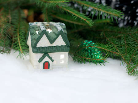 Snow-covered Christmas house with fir branches behind photo
