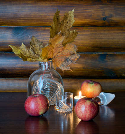 Crystal decanter with yellow maple leaves, glass, apples and burning candle photo
