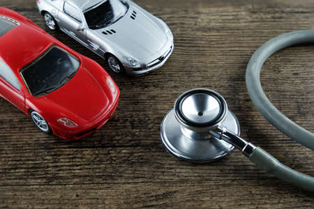 Stethoscope and car on the wooden background, Concept of car check-up, repair and maintenance.