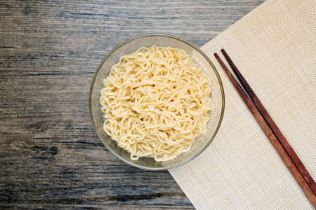 Top view of instant noodle in the glass bowl near the chopsticks on the wooden table