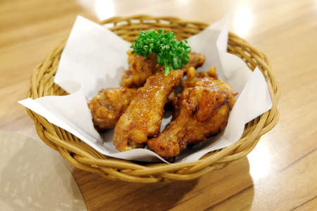 Fried chicken wings in white plate on wooden table. 写真素材