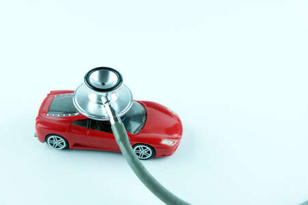 Stethoscope checking up the car on white background, Concept of car check up, repair and maintenance. 版權商用圖片