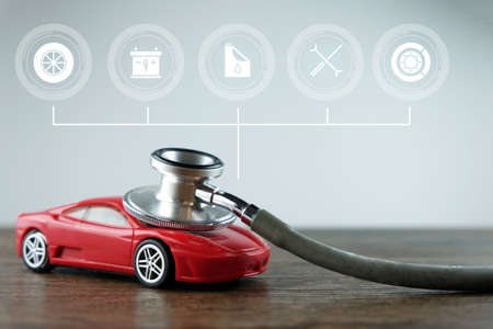 Stethoscope and car with service icons on the wooden background, Concept of car checking, repair and maintenance. Standard-Bild