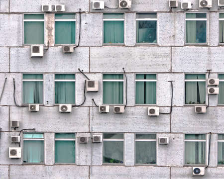 many air conditioners on the wall with windows