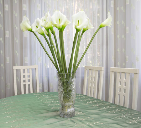 a bouquet of white calla lilies artificial flowers in a vase on the table in the interior photo