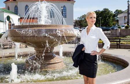 light hearted: Portrait of a business woman in a white fountain in summer day