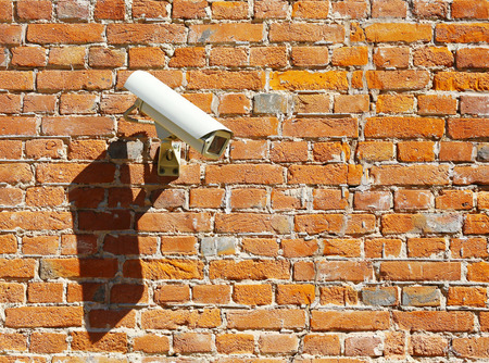 rural development: modern security camera on an old brick wall Stock Photo