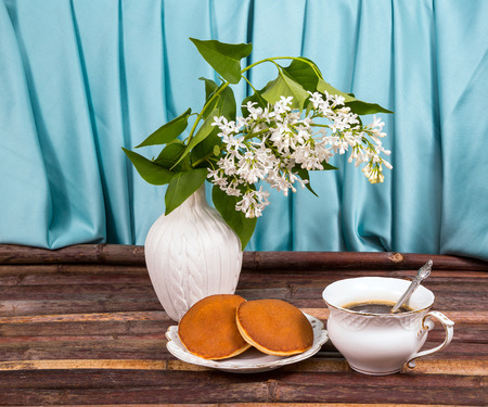 vase of lilacs on the table of the cane. coffee and cake. background, texture photo
