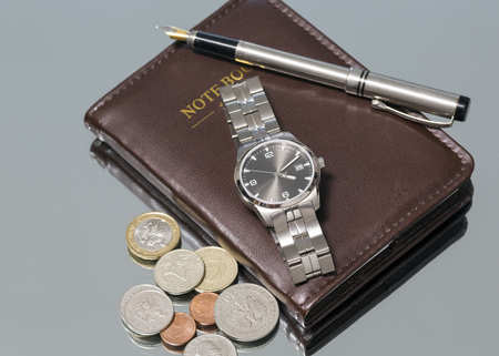 wrist watch: wrist watch metal coins pen. notebook. close-up. Macro. Stock Photo