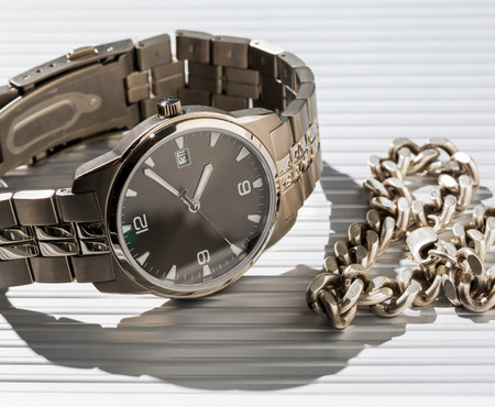 jewelry chain: Watches and jewelry chain on a light background. Business still-life