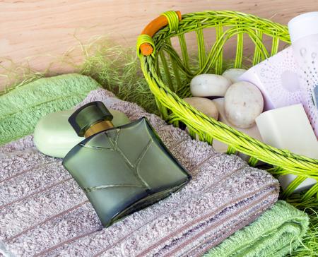 productos de aseo: Naturaleza muerta con toallas y art�culos de tocador en una cesta en un fondo verde. acercamiento Foto de archivo