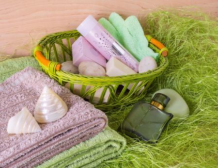 productos de aseo: Naturaleza muerta con toallas y artículos de tocador en una cesta en un fondo verde.