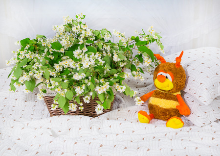 basket weaving: jasmine flowers in a basket and toy bee on a bed. background white curtains.