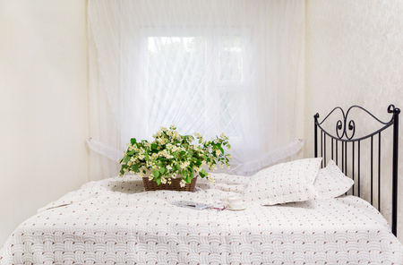 morning. jasmine flowers in a basket on the bed. background white curtains. bedroom. a fragment of an interior