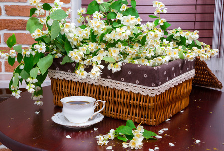 table of contents: coffee mug and jasmine flowers on a background of a wicker basket.