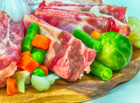 frozen meat: raw meat and frozen vegetables on a tray.  Stock Photo