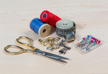 darning needle: Still life with scissors, thread, pin on a wooden table.  Stock Photo