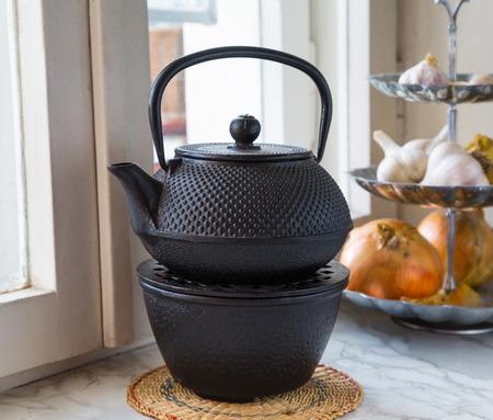 tetsubin: metallic teapot on the kitchen window. interior. vegetables, onions, garlic Stock Photo