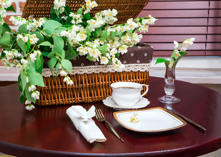 table of contents: dinner set, coffee mug and jasmine flowers on a background of wicker baskets.