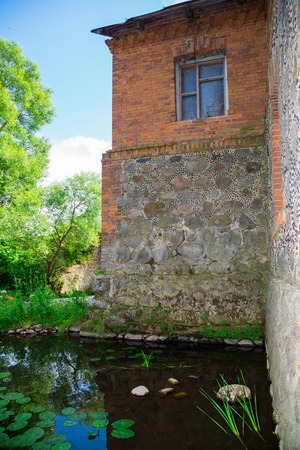 water mill: a fragment of a stone house near the water. an old water mill. architecture. architecture