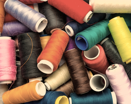 old spools: colorful spools of thread closeup. photo in old style image