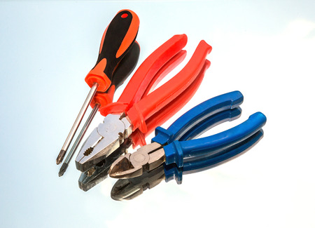 wire cutters: metal tools pliers, wire cutters, screwdriver, background on the mirror, the reflection of the sky.