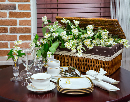table of contents: set of dishes, glasses, mug and jasmine flowers in the background wicker basket in the interior. wooden table. close-up Stock Photo
