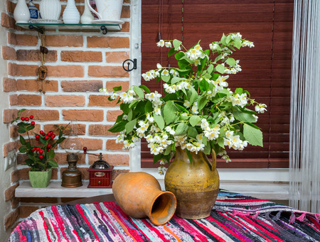 wood blinds: jasmine flowers in a jug on a background in interior design. wooden table. close-up Stock Photo