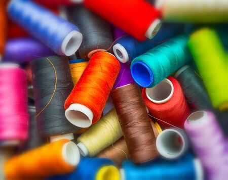 craft background: many colorful thread reels closeup. sewing, craft. background, wallpaper. blur on the edge, vignette filter Stock Photo