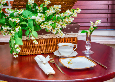 table of contents: dinner set, coffee mug and jasmine flowers on a background of wicker baskets. interior, wooden table.