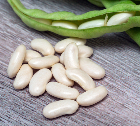 baccello verde fagioli bianchi close-up su un tavolo di legno. verdure, cereali. macro.