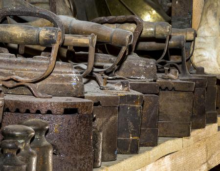 wooden shelf: Old rusty irons, wooden shelf, many objects. still life