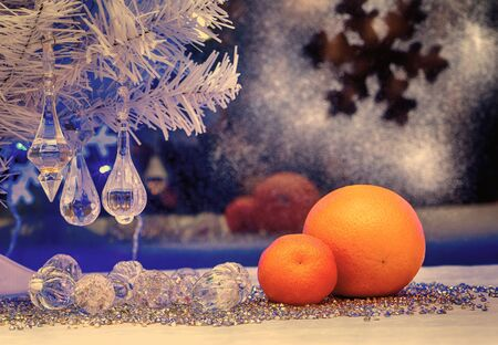 oldstyle: Christmas tree, mandarin, orange on the background of the winter window. Christmas holiday. blue light, vintage, retro, old style picture, photo old-style images, maps, wallpaper