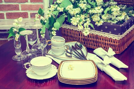 wood blinds: set of dishes, glasses, mug and jasmine flowers on a background of wicker baskets. interior, wooden table. close-up Stock Photo