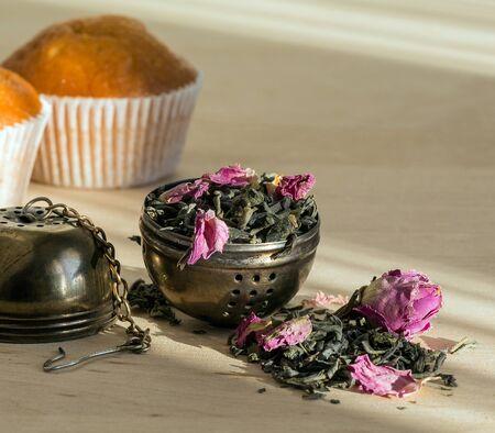 tea filter: tea leaves and rose petals and cylinder filter for brewing tea, sweet cupcake, dessert