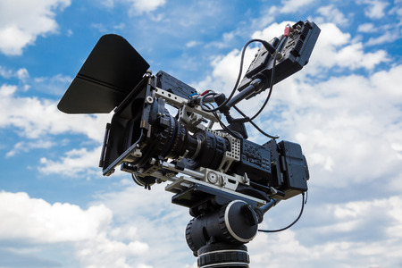 telecast: Professional video camera on a tripod against the blue sky