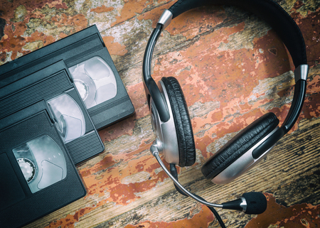 video cassette tape: video cassettes and headphones on a wooden table, retro style