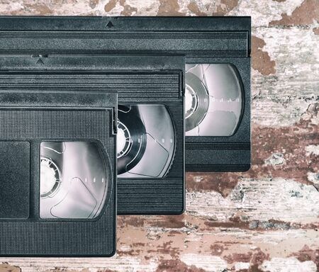 videocassette: three videocassette close up on a wooden surface, retro-style, old, record sound and images