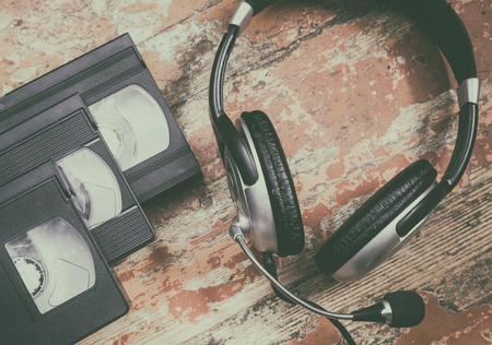 video cassette tape: video cassettes and headphones on a wooden surface, retro style Stock Photo