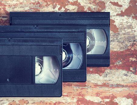 videocassette: tres cintas de vídeo de cerca sobre una superficie de madera, de estilo retro, viejo, grabar sonido e imágenes