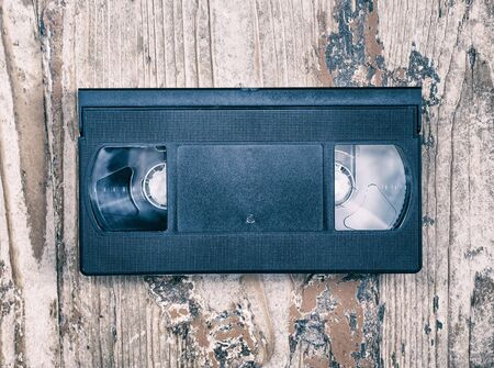 videocassette: video cassette close-up on a wooden surface, retro-style, old, record sound and images