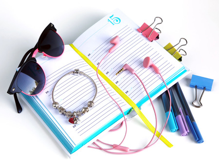 office tools: office tools notebook with pen, glasses, earphones and a clip for papers, still life Stock Photo
