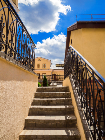 old stairs of concrete outdoors, black steel railing with a yellow wall, perspective, city, architecture Stock Photo