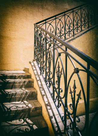 yellow wall: old stairs of concrete outdoors, black steel railing with a yellow wall, perspective, city, architecture,  retro style