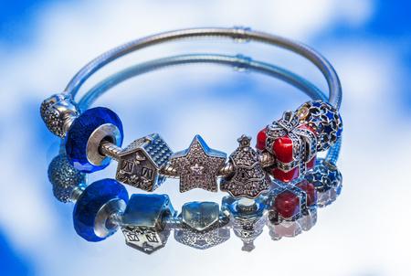a bracelet: jewelry bracelet female on a blue surface, modern fashion, charms, jewelry, macro