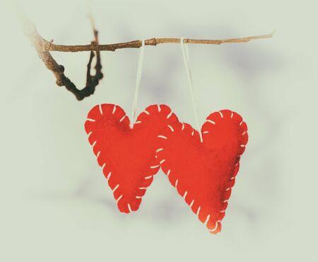 ahorcada: Corazón romántico rojo colgado en un bosque de arbustos nevados, invierno, día de San Valentín, tarjeta de vacaciones, estilo retro