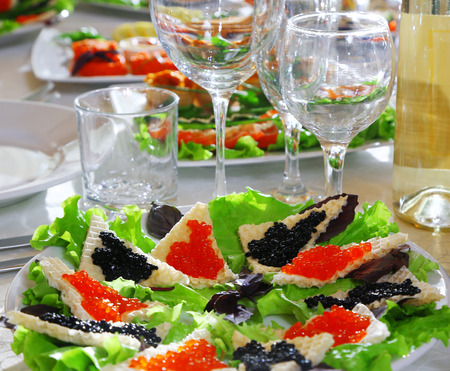 Decorated banquet table with various snacks and sandwiches with red and black caviar at a celebratory event or a wedding celebration Stock Photo
