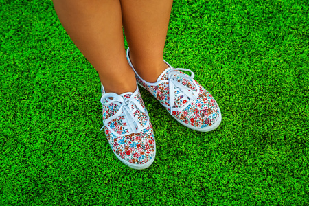 Feet in sneakers for walking outdoors. Conceptual image of a foot in shoes on green grass. Healthy lifestyle of a sporty woman, top view Stock Photo