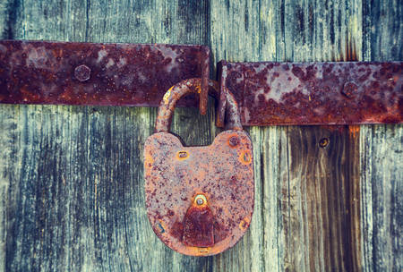 keep gate closed: metallic old rusty padlock on old wooden door, background, retro style